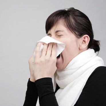 Frau mit akutem Infekt und Schal