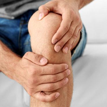 Mann mit Knieschmerzen und beiden Händen am Kniegelenk