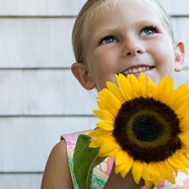 Kind mit Sonneblume und Heuschnupfen Allergie