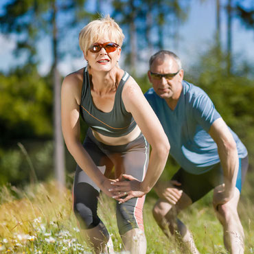 Paar dehnt sich vor einem Lauftraining um Sportverletzungen vorzubeugen