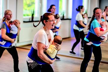 Mütter machen Sport mit Babys auf dem Arm. Tanzen zur Musik. Es macht allen Spaß.