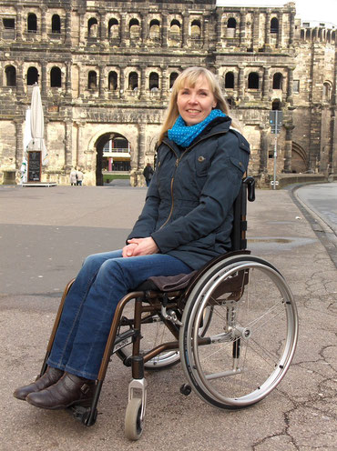 Melli im Rollstuhl vor der Porta Nigra / Melli in her wheelchair in front of the Porta Nigra