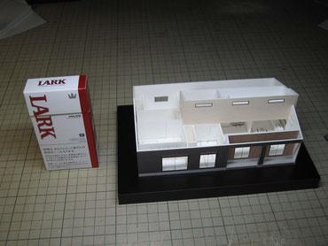 1/100住宅模型の隣に煙草の箱を置いて大きさの比較
