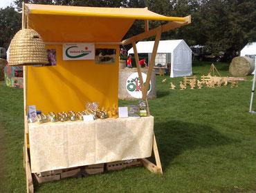 Wir verkauften unseren Honig am Verkaufsstand zusammen mit Honigbienenkerzen und Met. Zur Dekoration verwendeten wir einen Bienenkorb sowie eine gelbe Tischdecke und Bilder von Bienen und Imkerei.