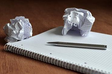 書き損じでぐしゃぐしゃに丸められたメモ書き。ノートとボールペン。