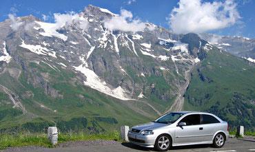 silbernes Auto auf Parkplatz vor teils noch schneebedeckten Bergen mit blauem Himmel und kleinen weißen Wolken