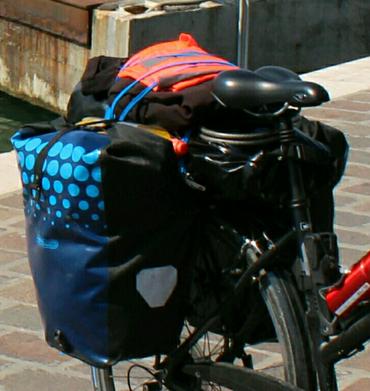 Ein Hinterrad mit zwei Taschen und diversen dazwischen befestigten Gegenständen