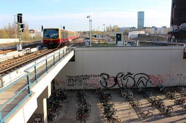 Verkehrknotenpunkt Ostkreuz Berlin: Eins S-Bahn fährt ein. Unter der Brücke geparkte Fahrräder. Foto: Helga Karl