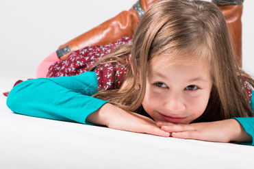 Studiofoto met witte achtergrond. <<<een meisje met lange haren liggend op de grond. Zij draagt een azuurblauwe shirt en een gebloemd kleedje.
