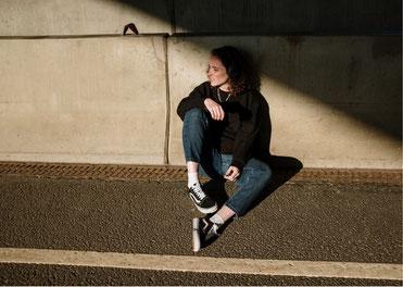 Junge Frau sitzt auf dem Asphalt mit ausgestreckten, leicht angewinkelten Beinen und schaut mit leicht zusammengekniffenen Augen, fragend und die Ferne.
