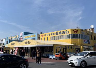 黄色の建物が回転寿司のお店。駐車場待ちの車が並ぶ。
