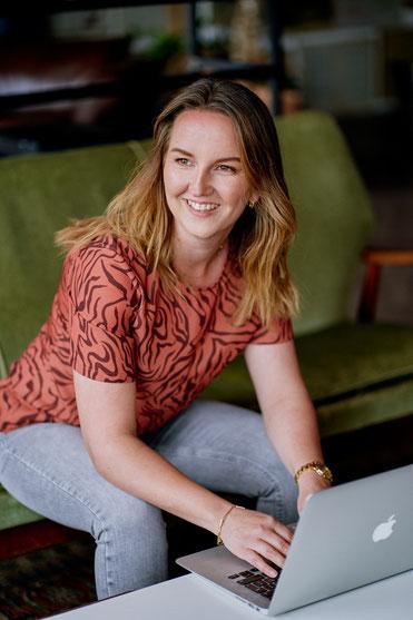 Roxanne Deurloo, sitting on sofa working on laptop smiling, leading light