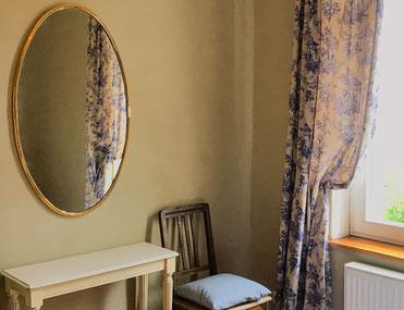 Detailaufnahme des Spiegels, Fensters und Beistelltisches im blauen Schlafzimmer der Ferienwohnung