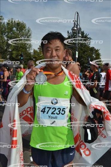 Youli mit der verdienten Medaille im Ziel des Berlin-Marathons ((c) Marathon-Foto)