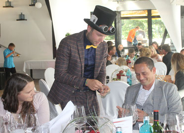 gespannte Gäste an langer Tafel mit Magier Johannes im Hintergrund