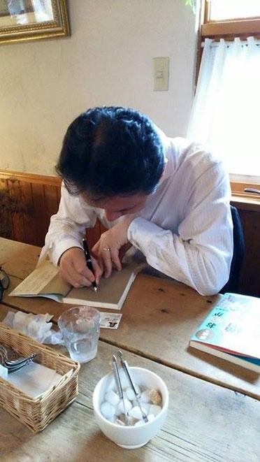 買って頂いた方の書籍にサインをする菅井さん