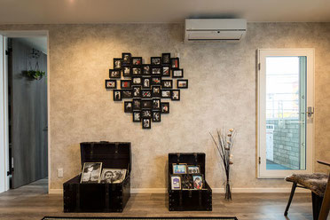 居間の壁に、額縁入の写真を並べてハート型にしている