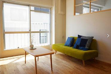 日のあたっている居間に、黄緑のソファと木製のテーブル