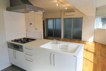 白を基調とした対面式キッチンから見える、広々とした居間