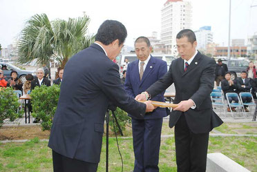 仲間代表世話人が渡辺さん(右)、菅沼さんに感謝状を贈呈した=14日午後、古賀辰四郎開拓記念碑前