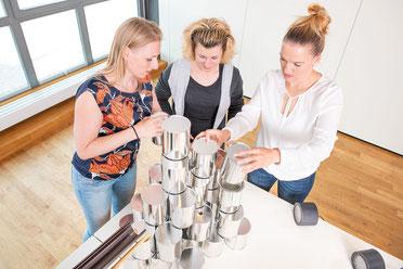 Teamevents in München: Drei Damen stapeln beim Teambuilding Blechdosen
