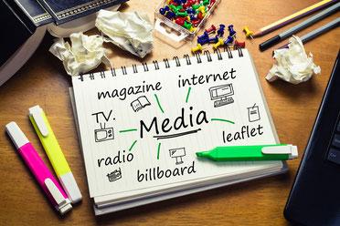 Phot d'un carnet de notes listant tous les médias de communication disponibles aujourd'hui. Autour du carnet, des surligneurs, un téléphone, des papiers chiffonnés, des punaises, des stylos et un livre entrouvert.