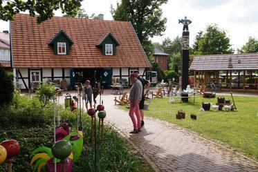 Auf dem gepflasterten Platz vor dem Dorfhaus im Fachwerkstil stellen regionale KünstlerInnen ihre farbenfrohen Arbeiten aus Ton, Metall und so weiter aus.