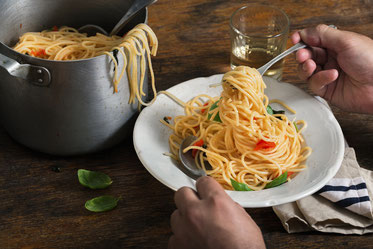 Topf und Teller mit großer, kalorienhaltiger Portion Spaghetti, aufgerollt auf Gabel.
