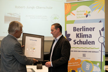 Als pädagogischer Leiter der Schulimkerei nahm Herr Dr. Erteld (rechts im Bild) die Urkunde entgegen. Die Auszeichnung wurde für die Aktivitäten zur Erhöhung der Biodiversität auf dem Schulgelände vergeben.