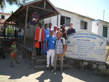 Bild 1: Der praktizierende Arzt Dr. Heuric Rakotomalala mit seinem Team, Frank Keppler mit Sohn Lucca vor dem Eingang zum Krankenhaus in Manambaro