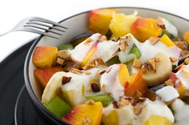 Schale mit gesundem Obstsalat mit Nüssen und Kernen, welche viel Omega-3, Eiweiß und andere Nährstoffe liefert.