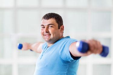 Mann trainiert seine Arme mit Hanteln zum Gewichtsverlust.