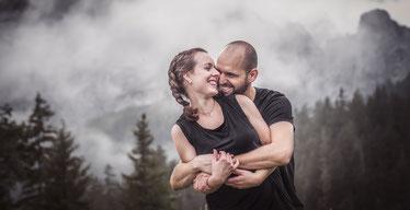 Verliebtes Paar steht vor einer Bergkulissen mit Nebel hält sich im Arm und lacht festgehalten von der Ostschweizer Familien Fotografin Monkeyjolie
