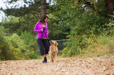 Frau mit Hund beim Joggen