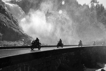 fünf Motorradfahrer auf einer Brücke mit Wasserfall im Hintergrund schwarz weiss