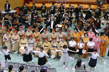 オーケストラに合わせKBG84が合唱を、小浜小学校児童が校歌ダンスを披露した=11日午後、小浜小中学校
