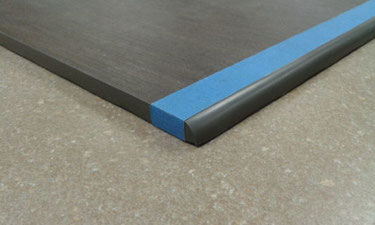 Dark charcoal tile with blue painters tape along a polished and rounded edge.