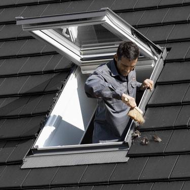 Laub und anderer Schmutz rund um ein Dachfenster sollten in regelmäßigen Abständen entfernt werden, damit das Regenwasser frei abfließen kann.  Foto: Velux Deutschland GmbH