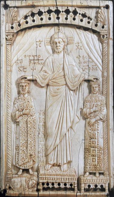 Elfenbeinrelief. Christus segnet oder krönt die links und rechts neben ihm stehenden Otto II. und Theophanu. Kaiser und Kaiserin sind deutlich kleiner dargestellt.
