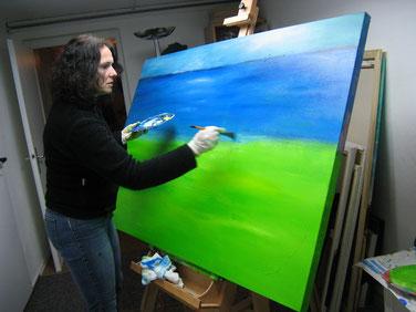 """Miriam Pietrangeli steht vor ihrer Staffelei und malt ein blau-grünes Landschaftsbild auf Leinwand, das sie """"Orizzonte"""" nennt"""