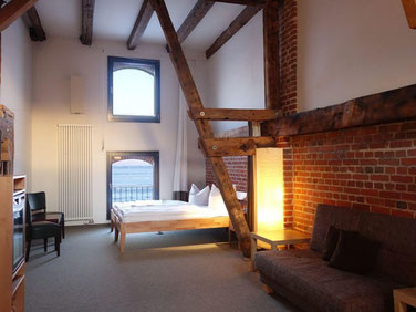 sleeping with view to the water of the sound in a the duplex suite Rügenbrücked of the hotel Hafenspeicher in Stralsund