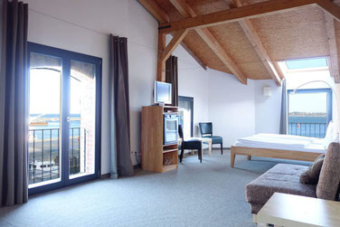sleeping with view to the sound in a the attic suite Hiddenseeblick of the hotel Hafenspeicher in Stralsund