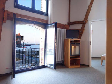 living with view to the water of the sound in the the duplex suite Querkanal of the hotel Hafenspeicher in Stralsund