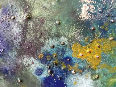 Schilderij in donkere tinten grijs, paars en groen en zilverkleur. Gebruikte materialen om reliëf te krijgen: sinaasappelnetje, dun verfrommeld papier, zand en strootjes.