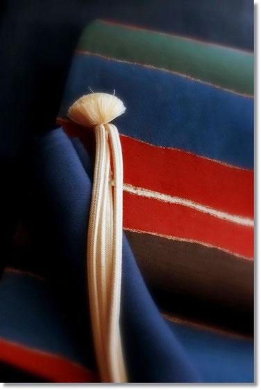 紺地無地結城に袋帯「ジャワ彩段文」。 緑・紺・赤・茶の配色が個性的な帯です。