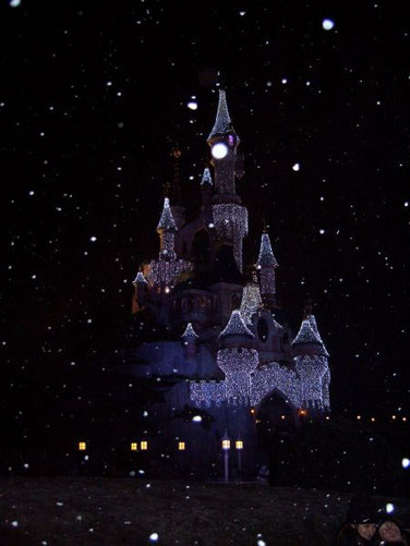 Beleuchtetes Schloss und fallender Schnee