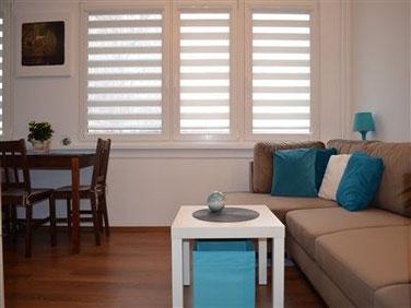 Wygodna sofa, ciemny stół drewniany, nowoczesne żaluzje, modne turkusowe dodatki, lampka, stolik kawowy, panele podłogowe, gładź gipsowa, białe ściany.