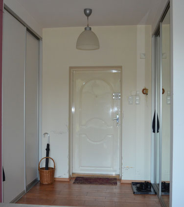 Stary przedpokój, brudne ściany, brak porządku, wnętrze wymaga stylizacji.