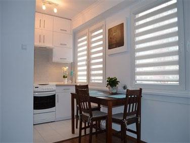 Połaczenie pokoju i kuchni. Białe ściany, nowoczesne szafki, ciemny stół, żaluzje i oświetlenie led,.