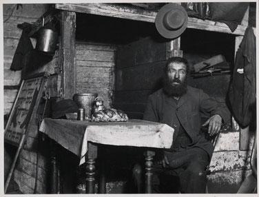 Schwarz-Weiss Foto aus den zwanziger Jahren, mit Mann in schäbiger Holzhütte